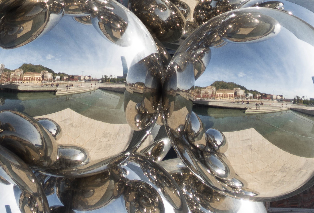A close-up of a big glass ball sculpture outside of the Guggenheim Museum.